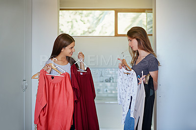 Buy stock photo Shot of a young woman helping her friend choose something to wear
