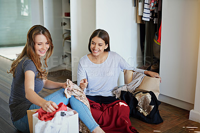 Buy stock photo Shot of two friends sititng in the bedroom looking through shopping bags of clothiing