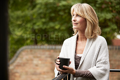 Buy stock photo Shot of a mature woman standing outside her home drinking coffee