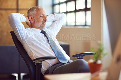 Buy stock photo Shot of a mature businessman relaxing at his desk in the office