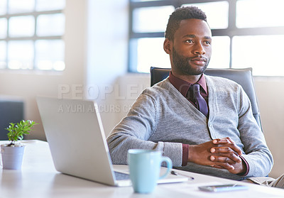 Buy stock photo Shot of a thoughtful young businessman sitting at his desk in an office