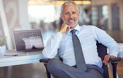 Buy stock photo Portrait of a mature businessman sitting at his desk in an office