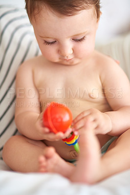 Buy stock photo Cropped shot of an adorable baby girl playing with a toy