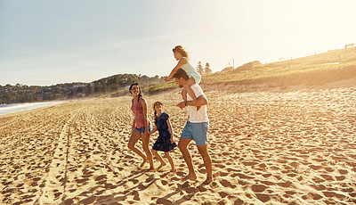 Buy stock photo Shot of a family of four walking on the beach