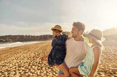 Buy stock photo Shot of a man spending some time at the beach with his two daughters