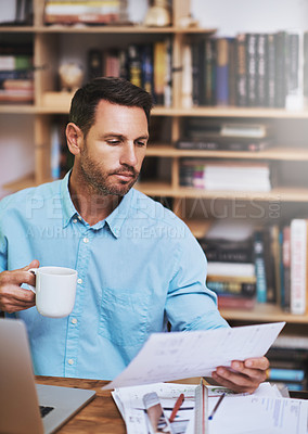 Buy stock photo Cropped shot of a businessman reading some paperwork at home