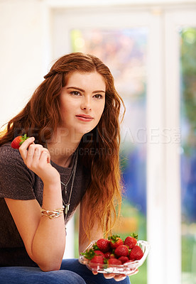 Buy stock photo Shot of a young woman eating fresh strawberries at home