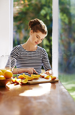 Buy stock photo Shot of a young woman slicing fresh oranges on a kitchen counter