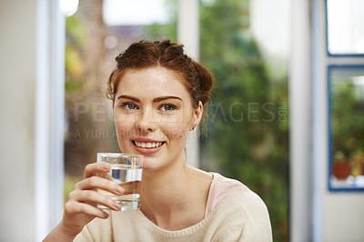 Buy stock photo Shot of a young woman drinking a glass of water at home