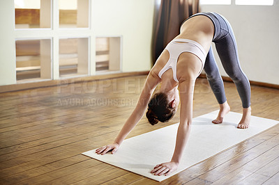 Buy stock photo A young woman doing the downward-facing dog pose during a yoga workout