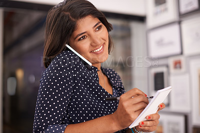 Buy stock photo Shot of an ambitious young woman talking on the phone and taking down notes in an office
