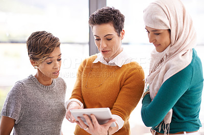 Buy stock photo Shot of a group of colleagues using a digital tablet in a modern office
