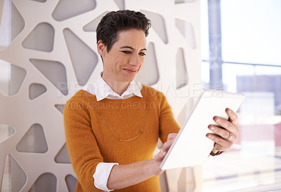 Buy stock photo Shot of a businesswoman using her tablet at the office
