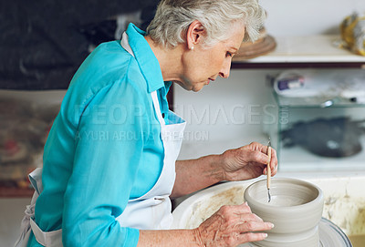 Buy stock photo Shot of a senior woman making a ceramic pot in a workshop