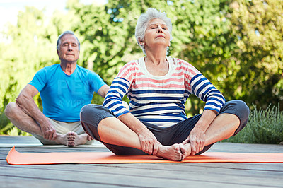 Buy stock photo Shot of a senior couple doing yoga together outdoors
