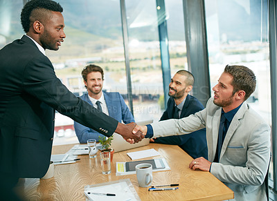 Buy stock photo Shot of businessmen shaking hands during a meeting
