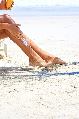 Buy stock photo Cropped shot of a young woman applying suntan lotion while relaxing at the beach