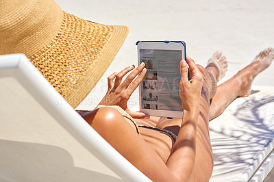 Buy stock photo Cropped shot of a young woman using her tablet while relaxing at the beach