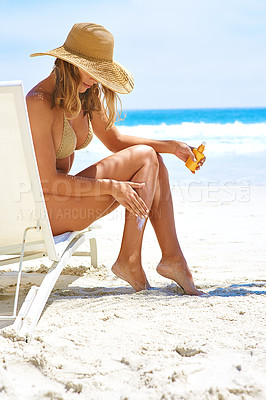 Buy stock photo Full length shot of a young woman applying suntan lotion while relaxing at the beach