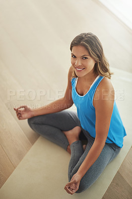 Buy stock photo High angle portrait of a young woman practicing the art of meditation at home
