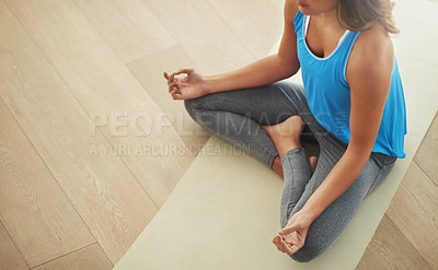Buy stock photo High angle shot of a young woman practicing the art of meditation at home