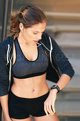 Buy stock photo Cropped shot of an attractive young athlete checking her watch after an outdoor workout
