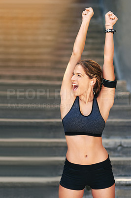Buy stock photo Cropped shot of an attractive young athlete standing with her arms raised after an outdoor workout