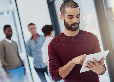 Buy stock photo Cropped shot of a young businessman working in the office with her colleagues in the background