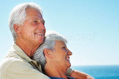 Buy stock photo Closeup of senior couple standing against sky with man embracing woman from behind