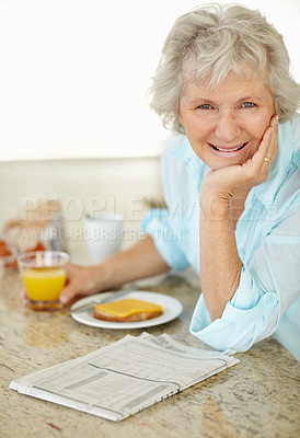 Buy stock photo Portrait of a senior woman having breakfast and reading the paper on the kitchen counter