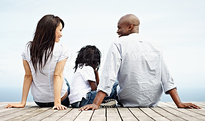 Buy stock photo Rearview shot of a young family sitting side by side on a boardwalk looking at the ocean