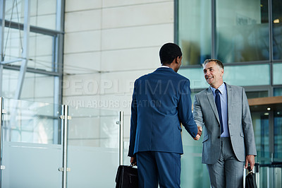 Buy stock photo Shot of two businessmen shaking hands in the lobby of an office building