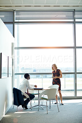 Buy stock photo Shot of two businesspeople talking in an office