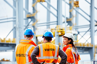 Buy stock photo Rearview shot of three workers talking while standing on a commercial dock