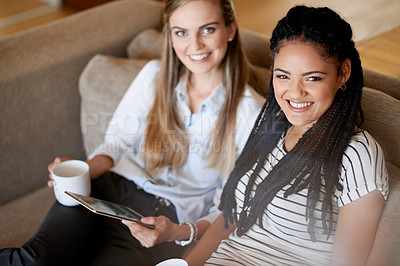 Buy stock photo Shot of two young friends having coffee while using a digital tablet together
