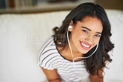 Buy stock photo Cropped portrait of a young woman listening to music while relaxing on her sofa at home