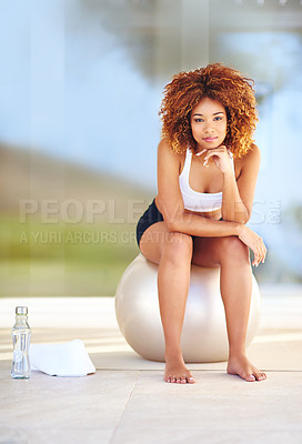 Buy stock photo Shot of a sporty young woman sitting on a swiss ball