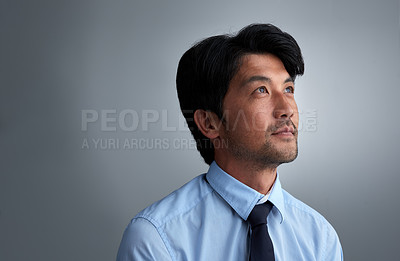 Buy stock photo Studio shot of a thoughtful businessman against a gray background