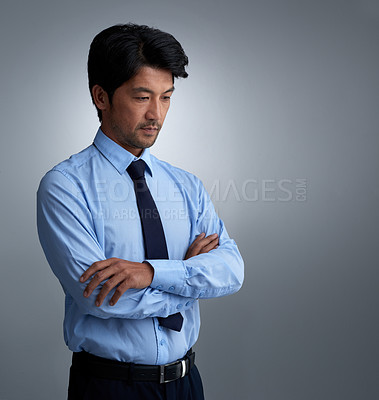 Buy stock photo Studio shot of a pensive businessman against a gray background