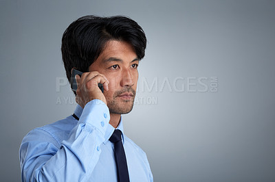Buy stock photo Studio shot of a businessman talking on a mobile phone against a gray background
