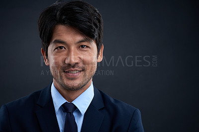 Buy stock photo Studio portrait of a confident businessman against a dark background