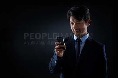 Buy stock photo Studio shot of a businessman using a phone against a dark background