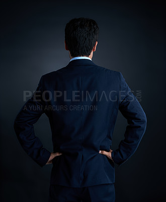 Buy stock photo Rearview studio shot of a businessman against a dark background