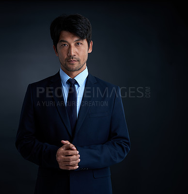 Buy stock photo Studio portrait of a serious businessman against a dark background