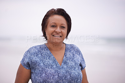 Buy stock photo Cropped shot of a mature woman at the beach on a misty morning