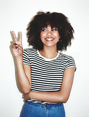 Buy stock photo Studio shot of a playful young woman showing the peace sign against a gray background