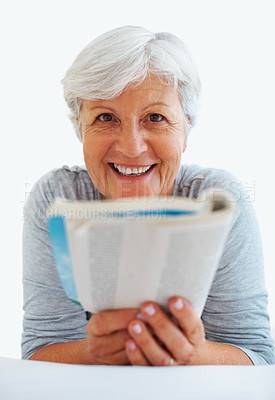 Buy stock photo Closeup portrait of senior woman lying in bed reading a book and smiling