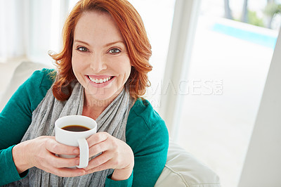 Buy stock photo Cropped portrait of a mature woman drinking coffee while relaxing on the sofa at home