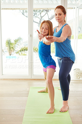 Buy stock photo Shot of a mother and daughter doing yoga together in the living room