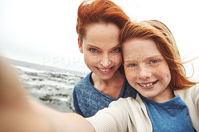 Buy stock photo Shot of a mother and her young daughter taking a selfie at the waterfront